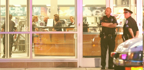 Police officers stand at the front door of an LA Fitness location after a shooting in Bridgeville, Pa. on Tuesday, Aug. 4, 2009. (AP / Tribune Review, Joe Appel)