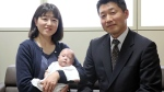 Ryusuke Sekino, a 5-month-old boy who was just 258 grams (9 ounces) when born, sits in the arms of his mother Toshiko Sekino, accompanied by his father Kohei Sekino, right, at a hospital in Azumino, Nagano Prefecture, central Japan. (Kyodo News via AP)