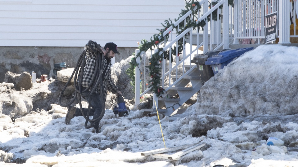 A resident carries a water pump after flooding from the Chaudiere River, Wednesday, April 17, 2019 in Beauceville, Que. Flooding forced the evacuation of 230 buildings and 36 people. THE CANADIAN PRESS/Jacques Boissinot