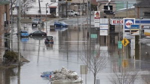 Flooded cars sit in the flooded main road, Tuesday, April 16, 2019 in Beauceville Que. THE CANADIAN PRESS/Jacques Boissinot