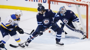 St. Louis Blues' Jaden Schwartz (17) scores the game winning goal against Winnipeg Jets goaltender Connor Hellebuyck (37) as Jets' Jacob Trouba (8) defends with 15 seconds left in the third period NHL playoff action in Winnipeg on Thursday, April 18, 2019. THE CANADIAN PRESS/John Woods
