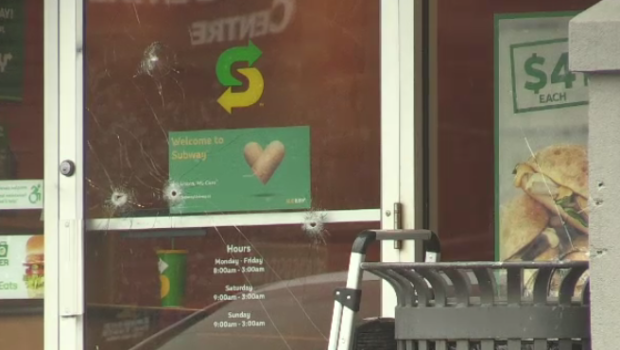 Bullet holes can be seen in the window of a Subway at the University Commons plaza.