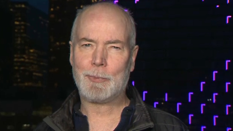 Douglas Coupland stands on the patio of Le Germain Hotel on April 19, 2019 as the bouncing ball sequence of Northern Lights is displayed on the TELUS Sky building