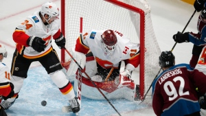 Colorado Avalanche left wing Gabriel Landeskog, right, has his shot bounce off Calgary Flames goaltender Mike Smith, center, and land between the skates of defenseman Travis Hamonic during the third period of Game 4 of an NHL hockey playoff series Wednesday, April 17, 2019, in Denver. The Avalanche won 3-2 in overtime. (AP Photo/David Zalubowski)