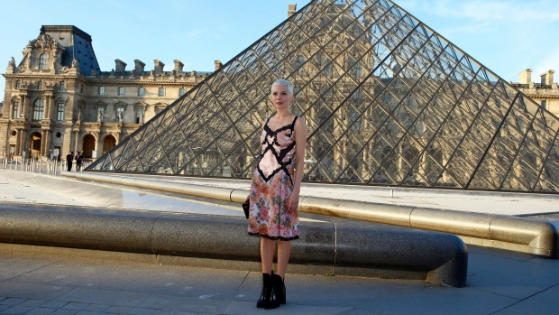 US actress Michelle Williams poses in front of the Louvre Pyramid in the main courtyard of the Louvre Palace during a photocall ahead of a diner for the launch of a Louis Vuitton leather goods collection in collaboration with US artist Jeff Koons, at the Louvre in Paris, Tuesday, April 11, 2017. (AP Photo/Francois Mori)