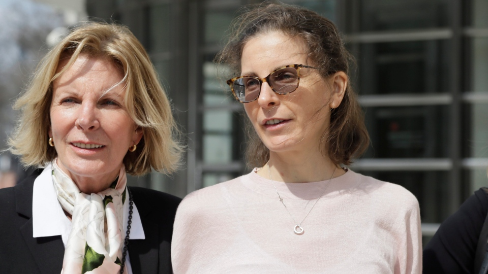 Clare Bronfman, right, a member of NXIVM, an organization charged with sex trafficking, leaves Brooklyn Federal Court, Monday, April 8, 2019, in New York. (AP Photo/Mark Lennihan)