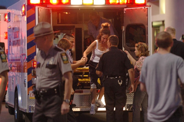 Emergency workers help a woman from the back of an ambulance after treating her in front of an LA Fitness location in Bridgeville, Pa. on Tuesday, Aug. 4, 2009. (AP / Tribune Review, Joe Appel)