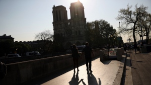 Two people walk by a the Notre Dame Cathedral in Paris, Saturday, April 20, 2019. (AP Photo/Francisco Seco)
