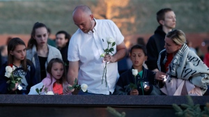 Will Beck, center, a sophomore who escaped during the shooting at Columbine High School nearly 20 years ago, joins his family in placing a rose on a plaque during a vigil at the memorial for the victims of the massacre Friday, April 19, 2019, in Littleton, Colo. (AP Photo/David Zalubowski)
