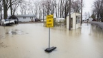 Floodwaters creep closer to homes on a residential street in the town of Rigaud, Que. west of Montreal, Saturday, April 20, 2019. THE CANADIAN PRESS/Graham Hughes