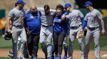 Toronto Blue Jays pitcher Matt Shoemaker, third from left, is helped off the field after sustaining an injury on a rundown play against the Oakland Athletics in the third inning of a baseball game Saturday, April 20, 2019, in Oakland, Calif. (AP Photo/Ben Margot)