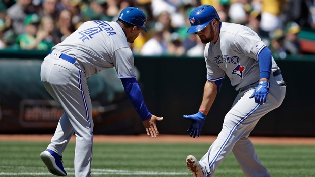 Toronto Blue Jays' Rowdy Tellez, right, is congratulated by third base coach Luis Rivera (4) after hitting a two-run home run off Oakland Athletics' Mike Fiers in the fourth inning of a baseball game Saturday, April 20, 2019, in Oakland, Calif. (AP Photo/Ben Margot)
