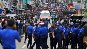 Sri Lankan police officers clear the road as an ambulance drives through carrying injured of Church blasts in Colombo, Sri Lanka, Sunday, April 21, 2019. (AP Photo/Eranga Jayawardena)