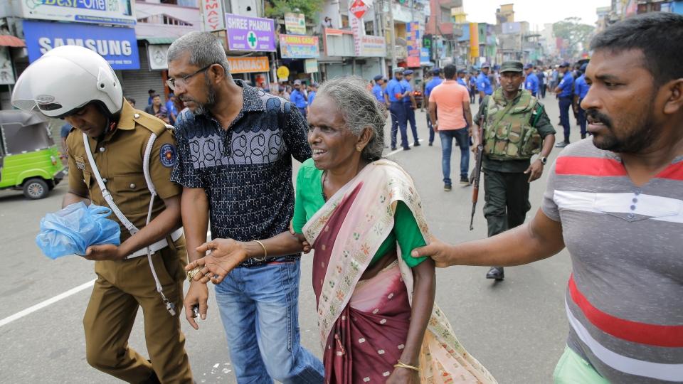A Sri Lankan elderly woman is helped near St. Anthony's Shrine after a blast in Colombo, Sri Lanka, Sunday, April 21, 2019. (AP Photo/Eranga Jayawardena)