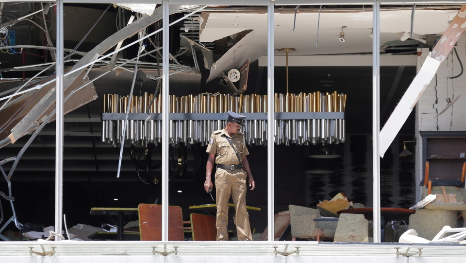A Sri Lankan Police officer inspects a blast spot at the Shangri-la hotel in Colombo, Sri Lanka, Sunday, April 21, 2019. (AP Photo/Eranga Jayawardena)