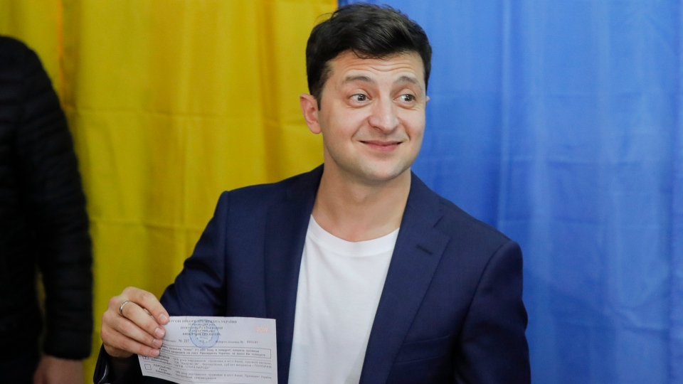 Ukrainian comedian and presidential candidate Volodymyr Zelenskiy shows his ballot before casting his ballot at a polling station, during the second round of presidential elections in Kiev, Ukraine, Sunday, April 21, 2019. (AP Photo/Vadim Ghirda)