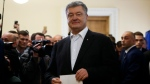 Ukrainian President Petro Poroshenko holds his ballot at a polling station, during the second round of presidential elections in Kiev, Ukraine, Sunday, April 21, 2019. Top issues in the election have been corruption, the economy and how to end the conflict with Russia-backed rebels in eastern Ukraine. (AP Photo/Efrem Lukatsky)