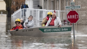People are evacuated by firefighters in a boat in Sainte-Marie, Que., Saturday, April 20, 2019. (THE CANADIAN PRESS / Jacques Boissinot)