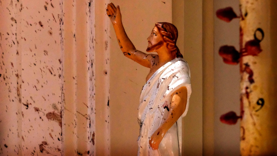 Blood stains are seen on the wall and on a Jesus Christ statue at the St. Sebastian's Church after blast in Negombo, north of Colombo, Sri Lanka, Sunday, April 21, 2019. (AP Photo)