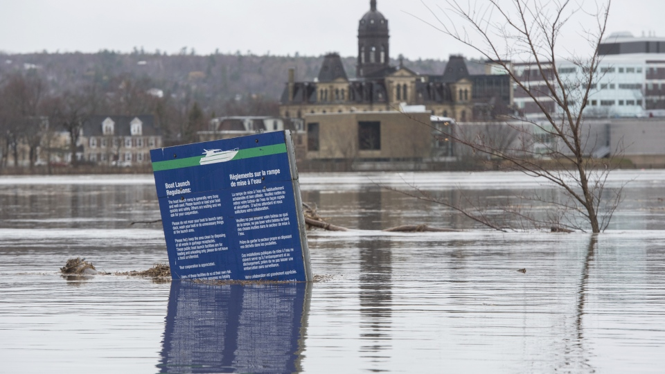 The New Brunswick Legislature is seen in the background of a boat ramp sign in Carleton Park surrounded by the flood water and debris from the St. John River in Fredericton, N.B. on Saturday, April 20, 2019. THE CANADIAN PRESS/Stephen MacGillivray
