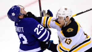 Toronto Maple Leafs defenceman Travis Dermott (23) and Boston Bruins centre Charlie Coyle (13) battle in front of the net during second period NHL playoff hockey action in Toronto on Sunday, April 21, 2019. THE CANADIAN PRESS/Frank Gunn
