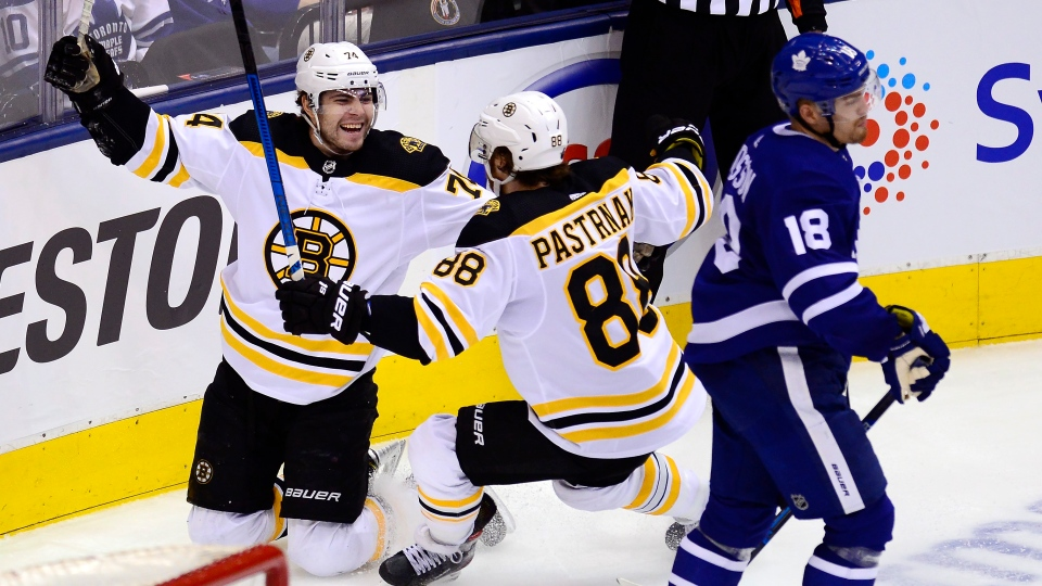 Boston Bruins left wing Jake DeBrusk (74) celebrates his goal with right wing David Pastrnak (88) as Toronto Maple Leafs left wing Andreas Johnsson (18) skates by during second period NHL playoff hockey action in Toronto on Sunday, April 21, 2019. THE CANADIAN PRESS/Frank Gunn