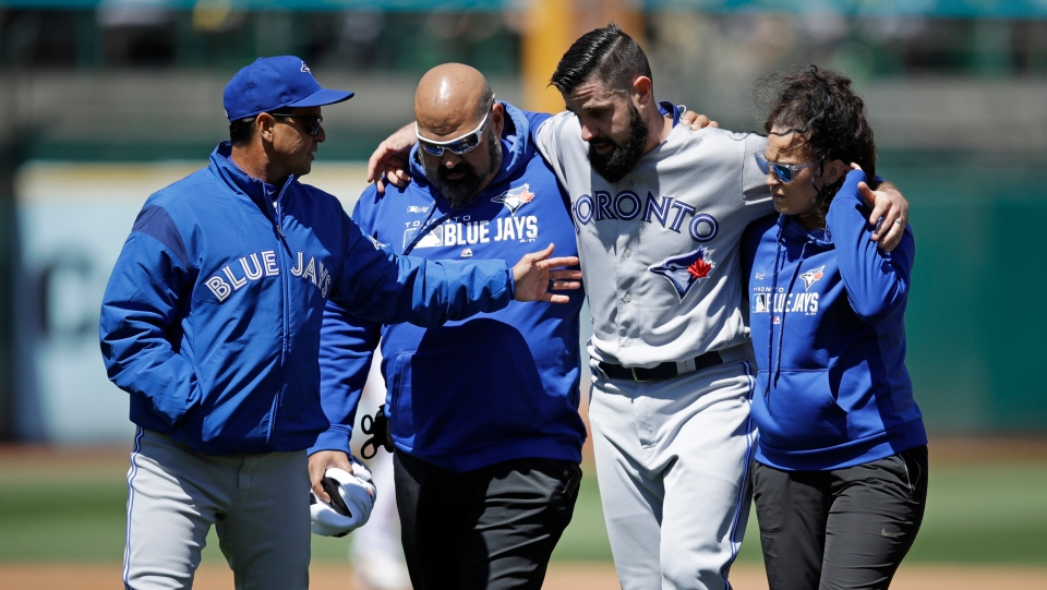 Toronto Blue Jays manager Charlie Montoyo, left, speaks with pitcher Matt Shoemaker, second from right, as Shoemaker is helped off the field after sustaining an injury during a rundown play against the Oakland Athletics in the third inning of a baseball game Saturday, April 20, 2019, in Oakland, Calif. (AP Photo/Ben Margot)