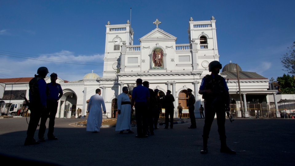 Sri Lankan air force officers and clergy stand outside St. Anthony's Shrine, a day after a blast in Colombo, Sri Lanka, Monday, April 22, 2019.  (AP Photo/Gemunu Amarasinghe)