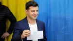 President-elect Volodymyr Zelenskiy shows his ballot before casting his ballot at a polling station, during the second round of presidential elections in Kiev, Ukraine, Sunday, April 21, 2019. Top issues in the election have been corruption, the economy and how to end the conflict with Russia-backed rebels in eastern Ukraine. (AP Photo/Vadim Ghirda)