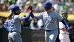 Toronto Blue Jays' Justin Smoak, right, is congratulated by Freddy Galvis (16) after hitting a two-run home run off Oakland Athletics' Ryan Buchter in the sixth inning of a baseball game Saturday, April 20, 2019, in Oakland, Calif. (AP Photo/Ben Margot)
