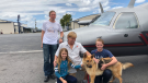 In this photo provided by the Humane Society of Broward County, kneeling from left to right, Chloe, Doug and Chase Peterson greet their long-lost German Shepherd dog Cedar on Saturday, April 20, 2019, at Fort Lauderdale Executive Airport, in Fort Lauderdale, Fla. (Cherie Wachter/Humane Society of Broward County via AP)