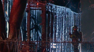 A firefighter examines water running off the roof of a car port that was set on fire in Saint Jean sur Richelieu (CTV Montreal/Stephane Gamache)