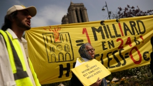 """People shout slogans during a protest in front of the Notre Dame cathedral in Paris, Monday, April 22, 2019. The yellow placard and banner reads in French: """"One billion in 24 hours! Homeless Zero"""" and """"Notre-Dame is roofless, we too!"""". (AP Photo/Francisco Seco)"""