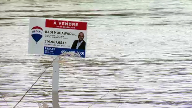 A 'for sale' sign sits on a flooded property in Laval in April 2019