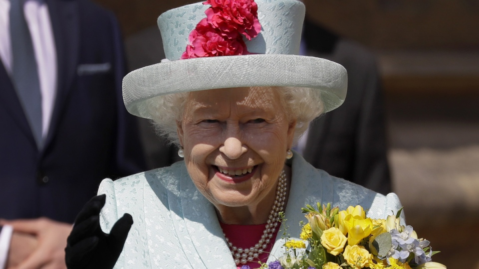 Queen Elizabeth II waves to the public as she leaves after attending the Easter Mattins Service at St. George's Chapel, at Windsor Castle in England, on April 21, 2019. (Kirsty Wigglesworth / AP)