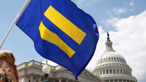 """In this July 26, 2017, file photo, a supporter of LGBT rights holds up an """"equality flag"""" on Capitol Hill in Washington. (AP Photo/Jacquelyn Martin, File)"""