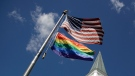A gay pride rainbow flag flies along with the U.S. flag in front of the Asbury United Methodist Church in Prairie Village, Kan., on Friday, April 19, 2019. (AP Photo/Charlie Riedel)