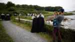 "In this June 13, 2014, file photo ""Game of Thrones"" fans stop for a picture on their way to Audleys field and castle, castleward, Strangford, Northern Ireland. Audleys field and castle was used for filming Season 1 as King Robert Baratheon and his retinue arrive at Winterfell. (AP Photo/Peter Morrison, File)"