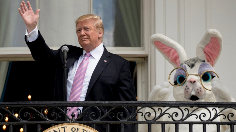 U.S. President Donald Trump, joined by the Easter Bunny waves from the Truman Balcony of the White House in Washington, Monday, April 22, 2019, during the annual White House Easter Egg Roll. (AP Photo/Andrew Harnik)