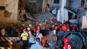 Rescuers carry a victim to a waiting ambulance after a 6.1 magnitude earthquake cause the collapse of a commercial building in Porac township, Pampangan province north of Manila, Philippines, Monday, April 22, 2019. (AP / Bullit Marquez)