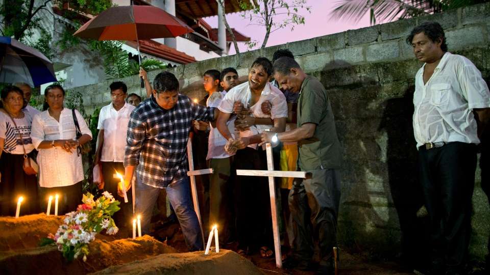 Relatives place flowers after the burial of three victims of the same family, who died at Easter Sunday bomb blast at St. Sebastian Church in Negombo, Sri Lanka, Monday, April 22, 2019. Easter Sunday bombings of churches, luxury hotels and other sites was Sri Lanka's deadliest violence since a devastating civil war in the South Asian island nation ended a decade ago. (AP Photo/Gemunu Amarasinghe)