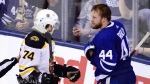 Boston Bruins left wing Jake DeBrusk (74) exchanges words after being hit into the end boards by Toronto Maple Leafs defenceman Morgan Rielly (44) during third period NHL playoff hockey action in Toronto on Sunday, April 21, 2019. (THE CANADIAN PRESS/Frank Gunn)