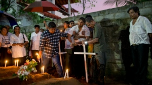 Relatives place flowers after the burial of three victims of the same family, who died at Easter Sunday bomb blast at St. Sebastian Church in Negombo, Sri Lanka, Monday, April 22, 2019. (AP Photo/Gemunu Amarasinghe)