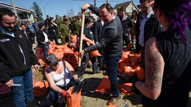 Quebec Premier Francois Legault helps make a sandbag as he visits a flooded area on Rue Saint-Louis in Gatineau, Que., on Monday, April 22, 2019. THE CANADIAN PRESS/Justin Tang