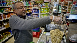 Dhannitha Meemanage, from Sri Lanka, bags cashews in his family's grocery store, in New York's Staten Island's 'Little Sri Lanka' community, Monday, April 22, 2019. (AP Photo/Bebeto Matthews)