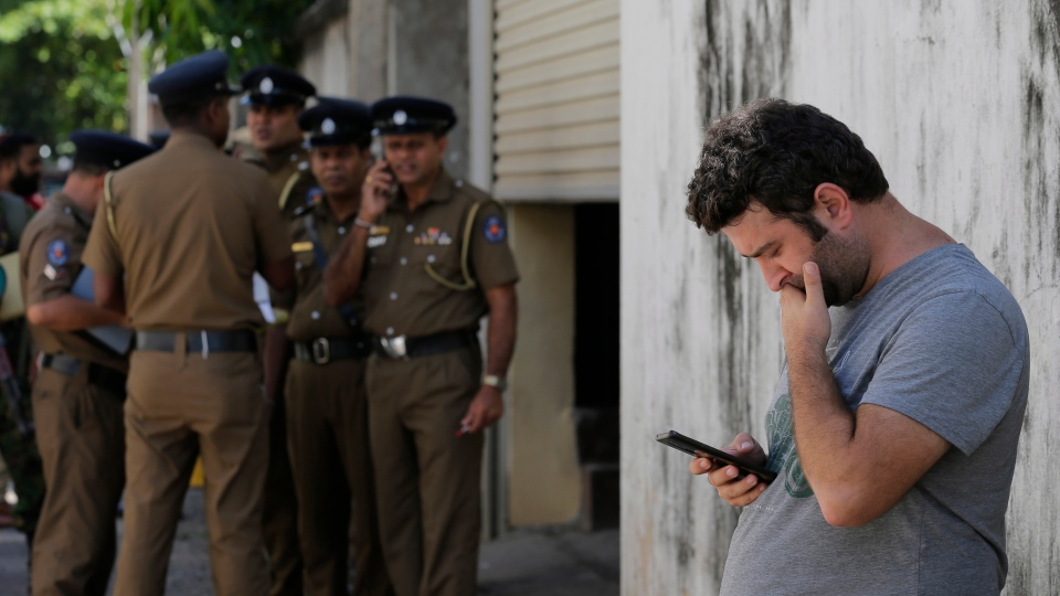 A foreigner checks his mobile phone while waiting outside a mortuary of a hospital, a day after series of blasts, in Colombo, Sri Lanka, Monday, April 22, 2019. (AP Photo/Eranga Jayawardena)
