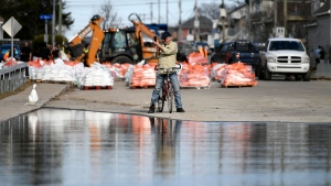 Pierre Bigras, whose father lives nearby, takes a photo from the edge of floodwaters on Rue Saint-Louis in Gatineau, Que., on Monday, April 22, 2019. THE CANADIAN PRESS/Justin Tang