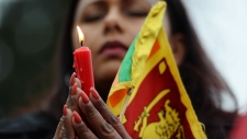 A woman holds a candle during a vigil honouring the victims of the bombings in Sri Lanka in Surrey, B.C. on Monday, April 22, 2019. THE CANADIAN PRESS/Jonathan Hayward
