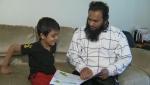 Sarjoon Abdul-Cader, a U of C PhD student who has halted his studies while awaiting a kidney transplant, reading a story with his five-year-old son