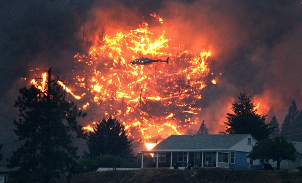 A helicopter starts a controlled burn behind an evacuated home in an attempt to reduce the amount of fuel for a wildfire burning on Mount McLean in Lillooet, B.C., on Tuesday August 4, 2009. (CP/Darryl Dyck)